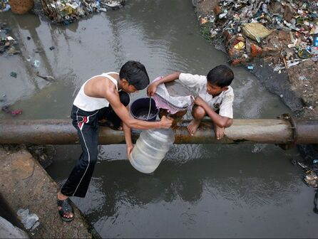 Two kids collecting water from polluted source